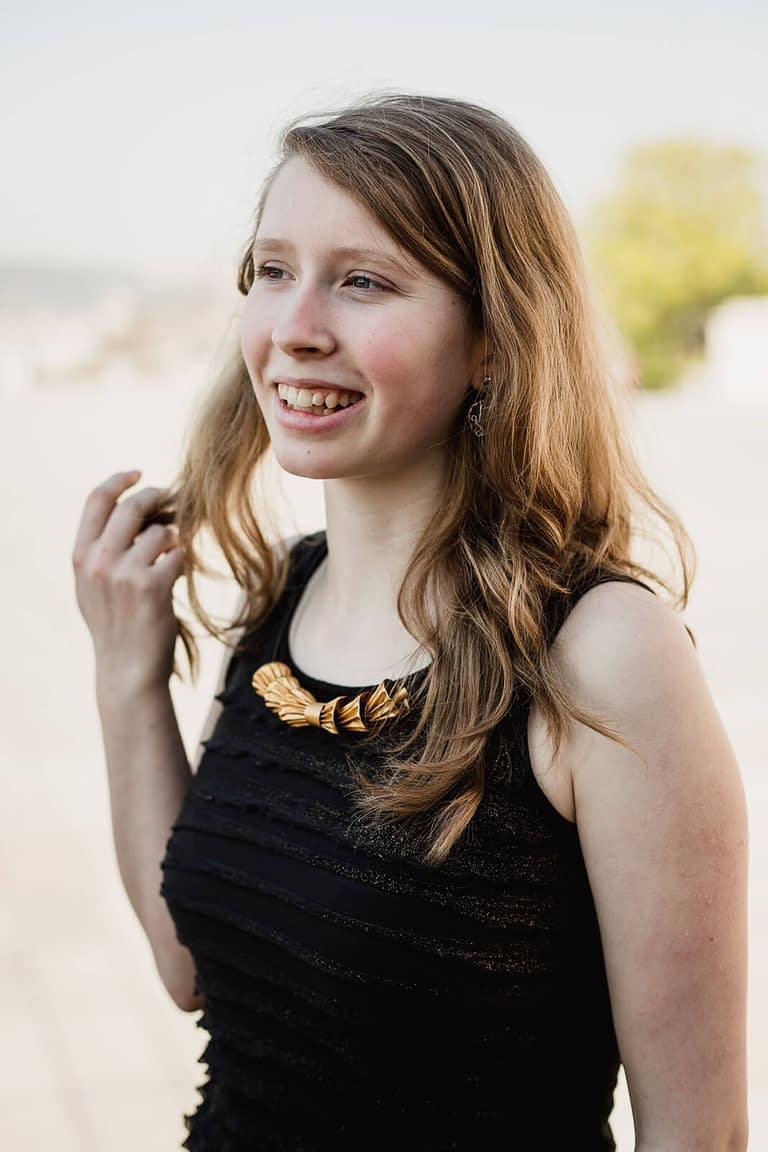 Zamyšlená dívka s velmi elegantním náhrdelníkem z kapslí