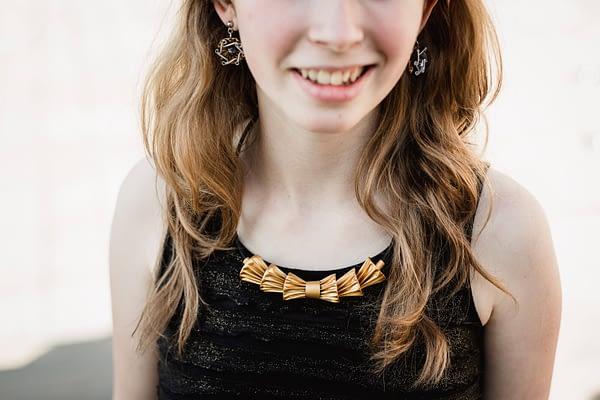 Dívka má na sobě náhrdelník styl mašle a náušnice upcyklované z kapslí
