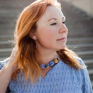 zasněná žena s modro-zlatým náhrdelníkem z kolekce Erika